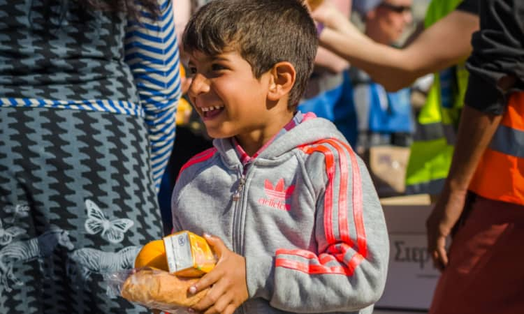 Syrian boy receive oranges from Charitable Organizations in a COVID-19 refugee camp