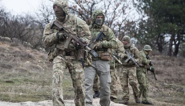 Military mercenaries group in camouflage military uniform and mask