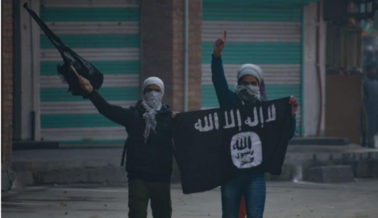 Kashmiri masked protester waving flags during clashes in Nowhattah Srinagar after Friday prayers on 21st December 2018