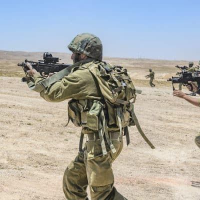 Israeli army combat soldiers firing while charging on terror targets